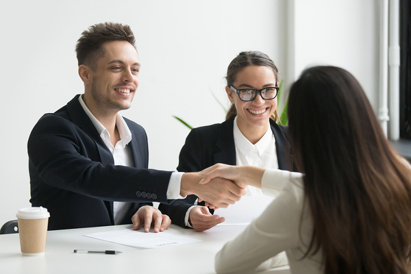 Interviewer shaking hands with a potential job candidate.