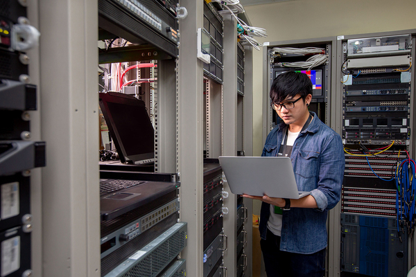 Computer technician working in a server room.