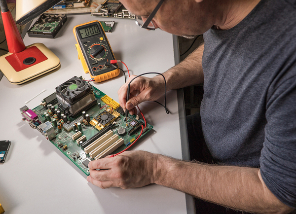 Computer technician working on a computer board.