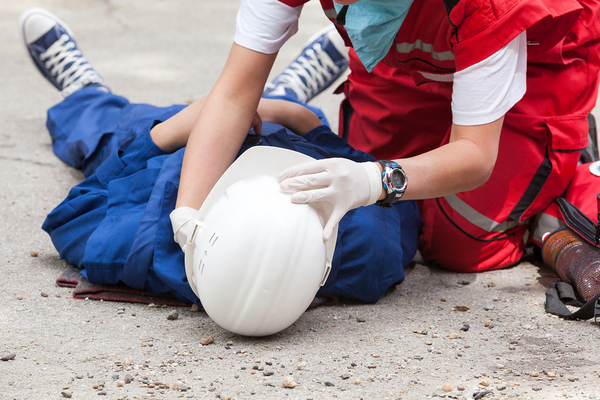 Construction supervisor assisting a worker lying on the ground