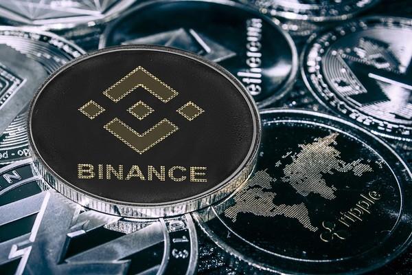 Silver coin with Binance logo.