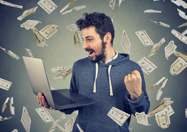 Man standing holding his laptop with cash falling down around him.