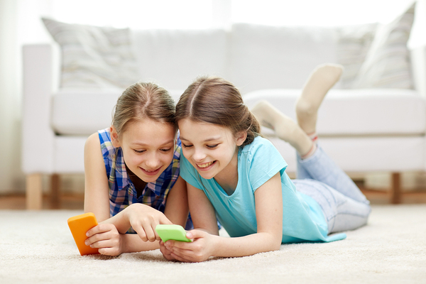 Two girls laying on the floor looking at their smartphones laughing