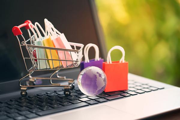 Miniature shopping cart with shopping bags.