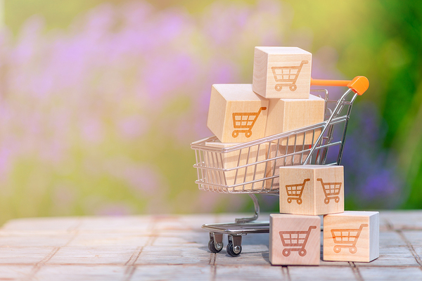 Miniature shopping cart filled with small packages.