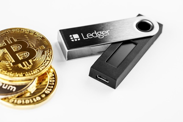 Gold coins with the bitcoin symbol and Ledger hardware wallet.