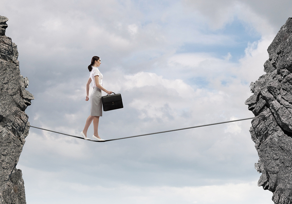 Woman walking a tightrope with a briefcase.
