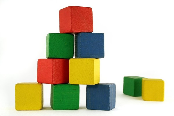 Red, green and blue wooden blocks in a pyramid.