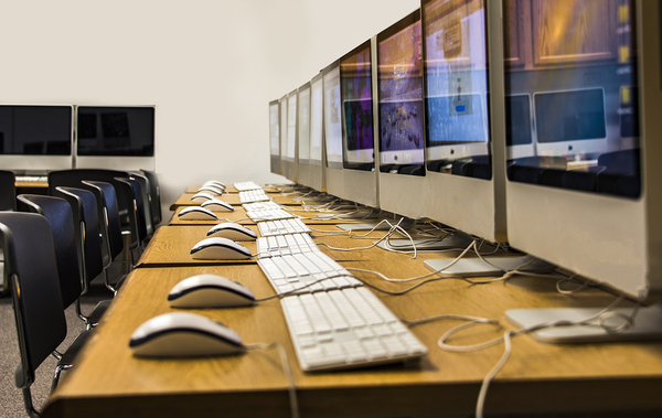 Row of iMacs on multiple desks with keyboards and mice Rameez Khizer, IT Marketing