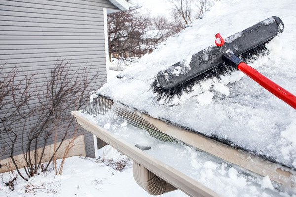 Brushing snow off a roof.