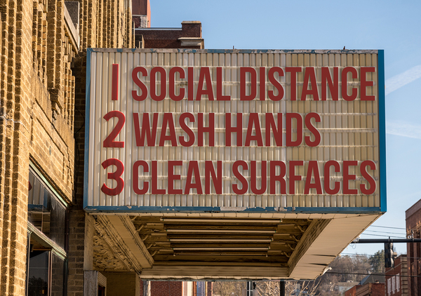 Movie Theatre sign listing social distance, wash hands and clean surfaces.
