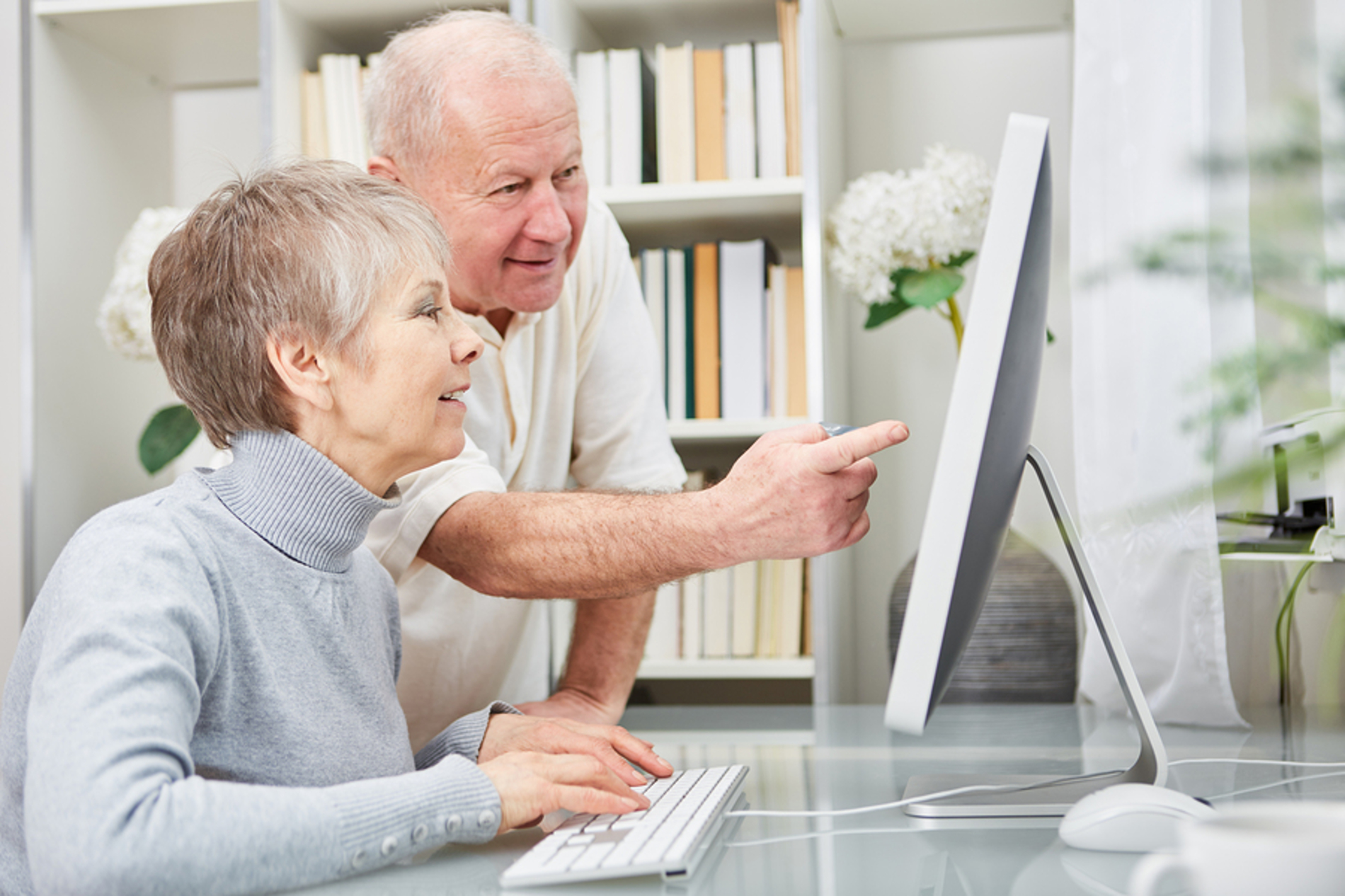 Elderly couple looking at a desktop computer together.