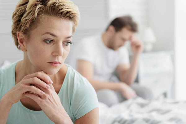 Woman looking down disappointed with man in the background with his hand on his forehead looking upset.