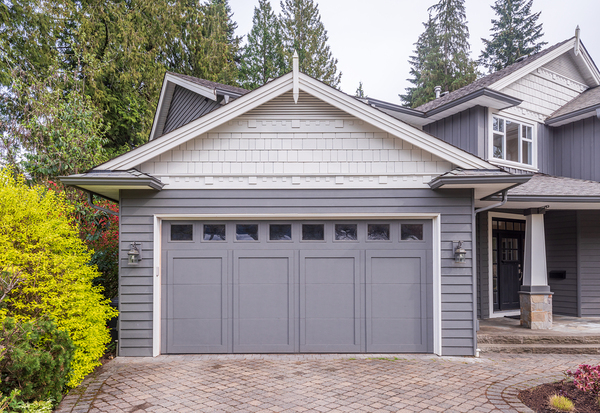 One car garage attached to a home colored grey and white.