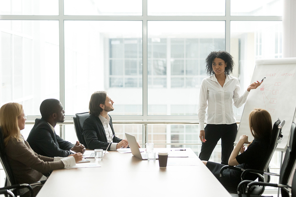 Woman presenting information to a group around a conference room.