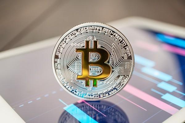 Silver coin with a gold bitcoin symbol.