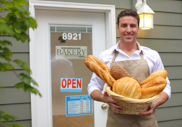 Bakery shop owner holding a basket filled with bread outside the entrance.