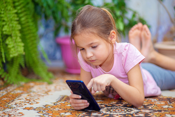 Young girl lying on the floor typing on a phone.