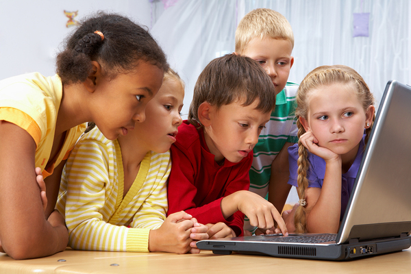 Group of children looking at a laptop computer screen.