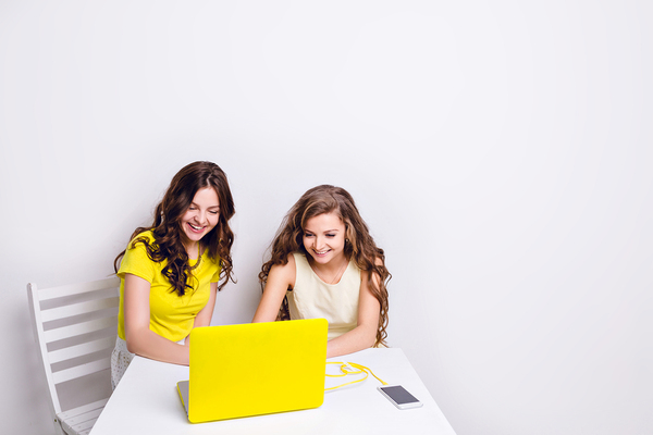 Two teens smiling while looking at a laptop screen.