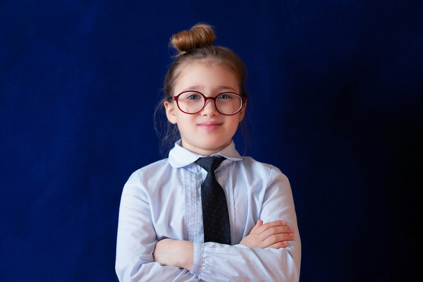 Girl standing with her hands crossed wearing glasses.