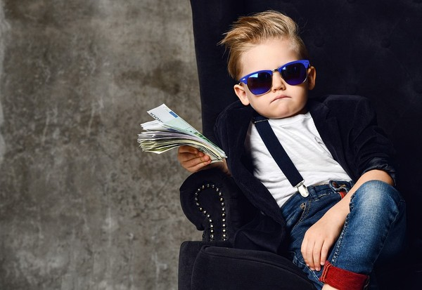 Cool child sitting in a chair with sunglasses and a stack of cash.