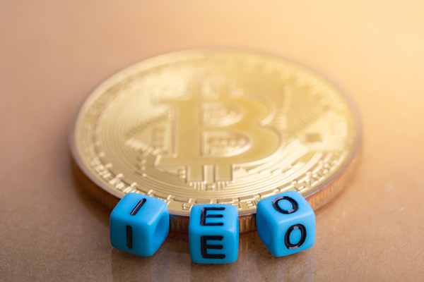 Gold coin with bitcoin symbol and dice spelling IEO.