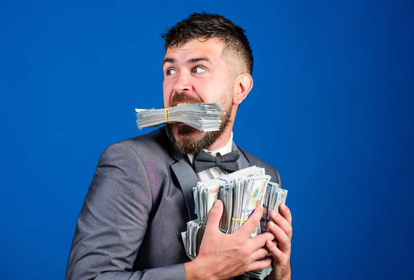 Man with stacks of cash in hands and mouth.