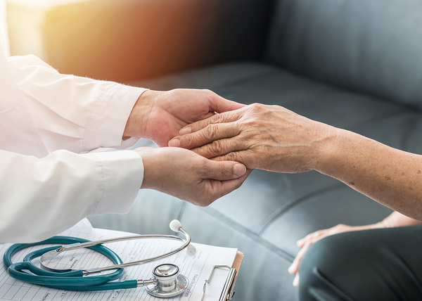 Medical doctor holding a patient's hand.
