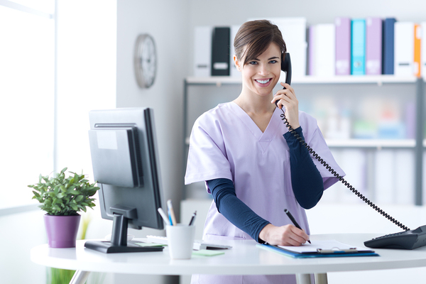 Happy receptionist on phone with patient.