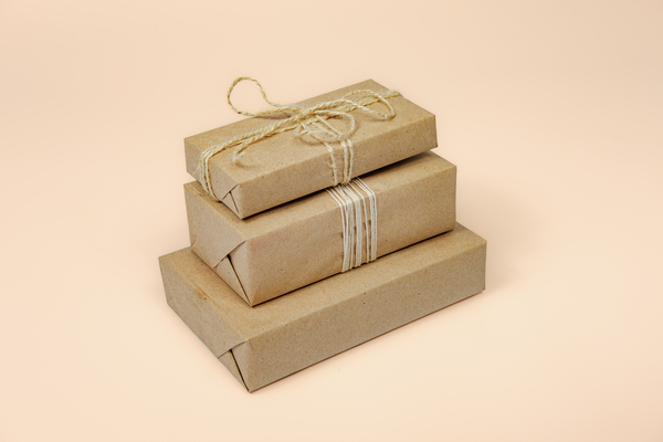 Brown paper packages tied up with strings in a stack.