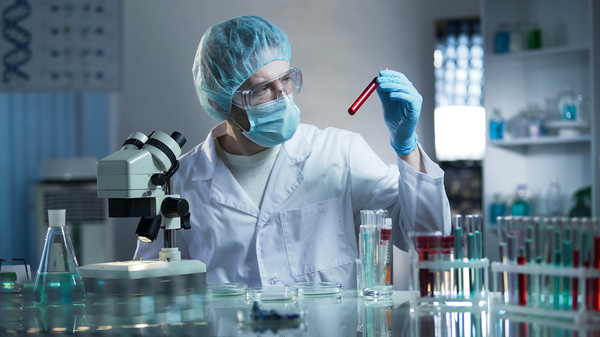 Man in a lab with vials and microscope.