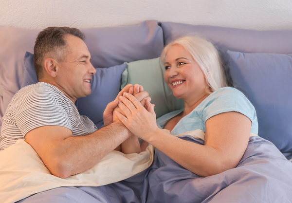 Man and woman lying in bed holding hands.