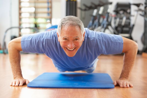 Older man performing a push up smiling.