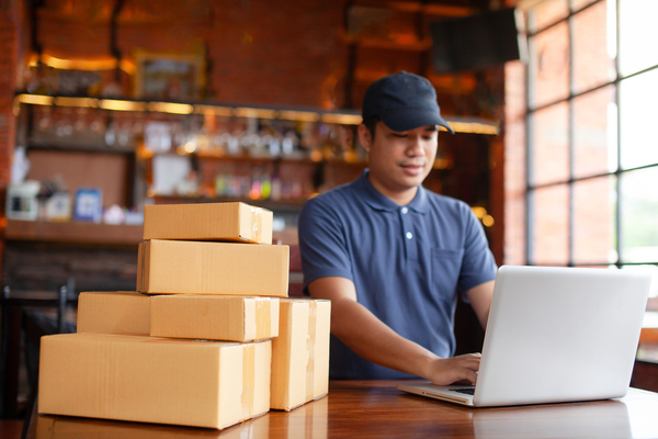 Man typing on a laptop with a pile of packages next to him.