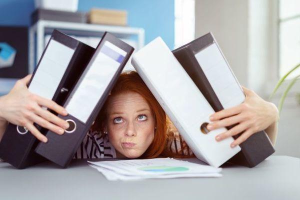 Woman holding multiple binders.