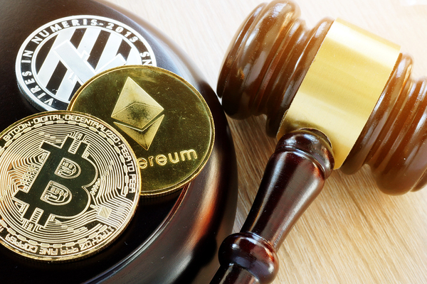 Gavel with gold coins labeled bitcoin, ethereum and litecoin.