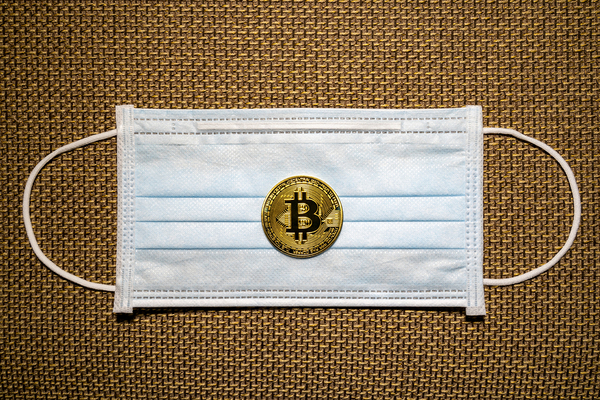 COVID-19 facemask with gold coin labeled with a bitcoin symbol.