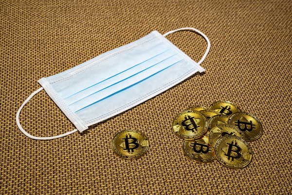 Facemask next to pile of gold coins with bitcoin symbols.