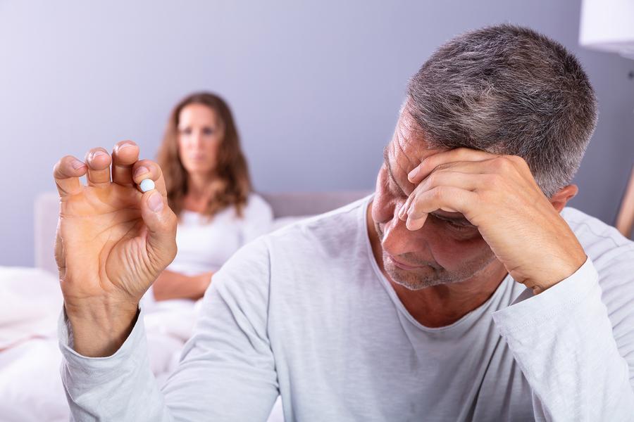 Man holding a blue pill.