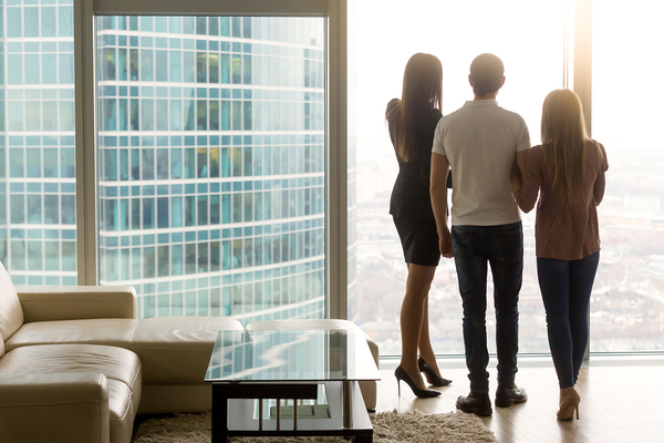 Three people looking out of a high rise building's window.
