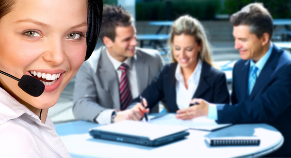 Woman smiling with a headset and a group of people in the background working at a table.