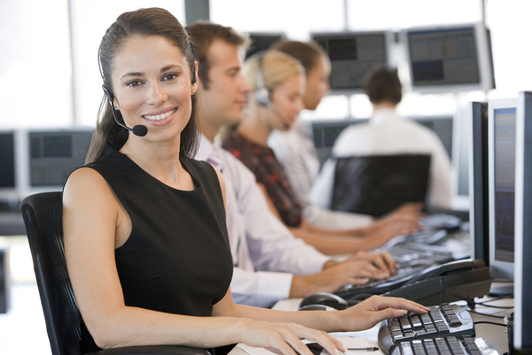 Woman on with a headset in front of a desktop computer.