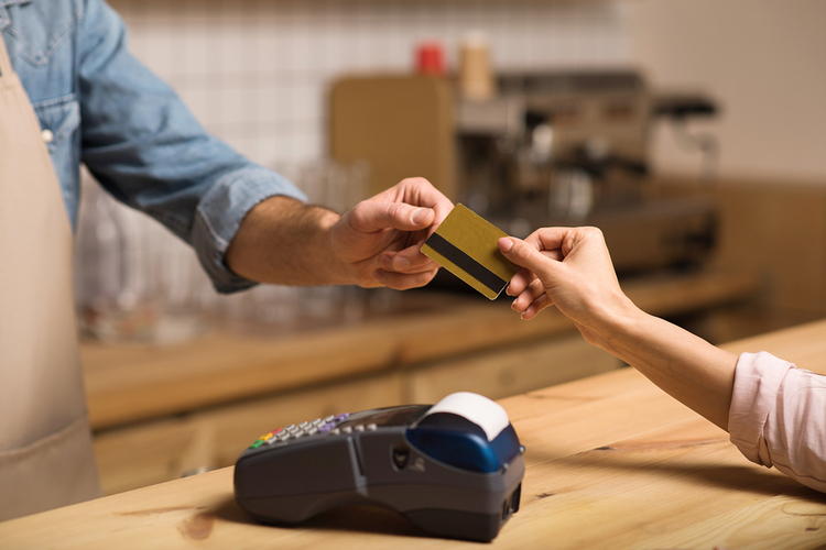 Making a purchase at a cafe with a credit card.