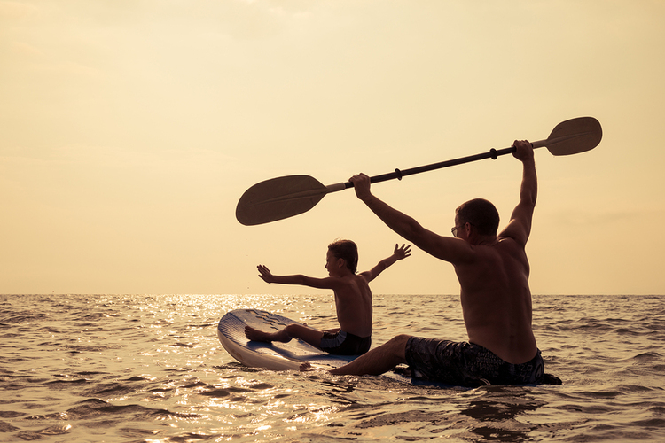 Two people on a surfboard.