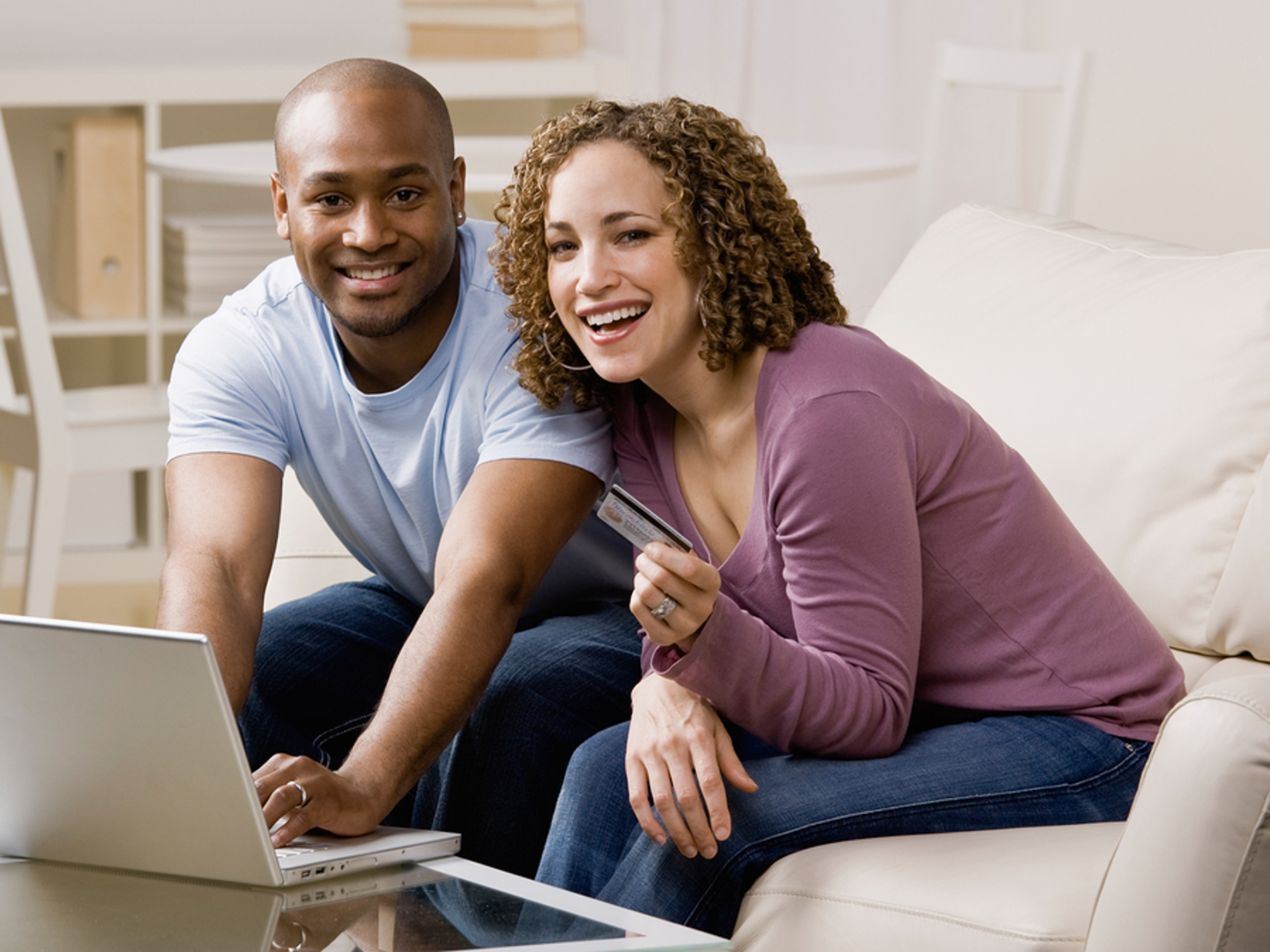 Couple using a credit card to purchase an item online.