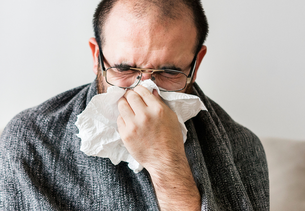 Man blowing his nose into a tissue.