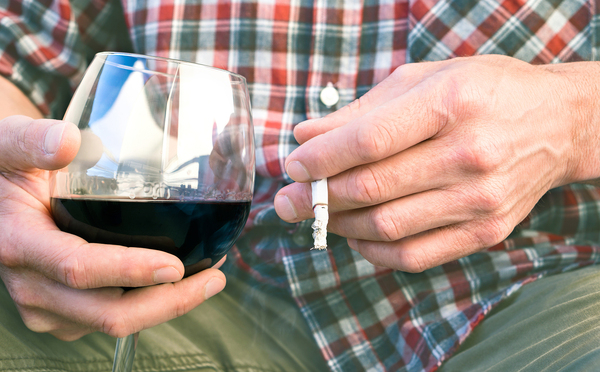 Man smoking a cigarette and drinking a glass of wine.