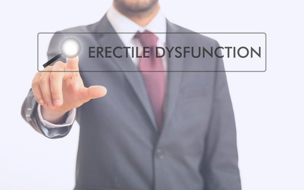 Man in a business suit pointing to the words Erectile dysfunction.