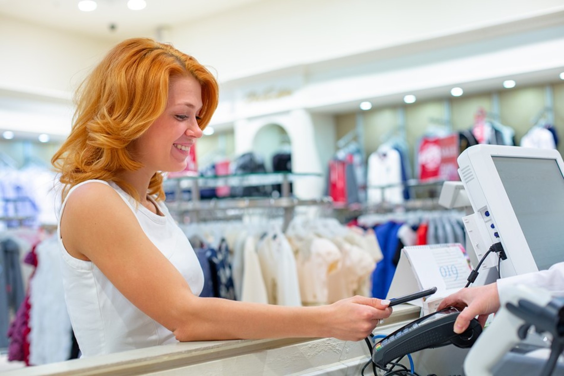 Smiling woman paying for clothing purchase at a register.